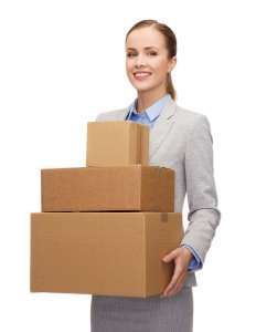 smiling businesswoman holding cardboard boxes